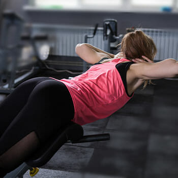 woman in a glute-ham raise position in a gym