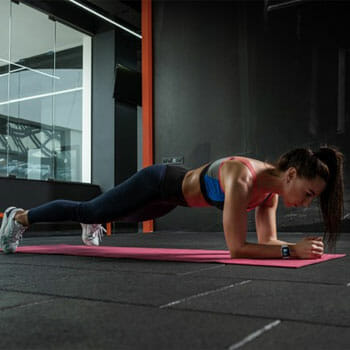 woman in a plank position in a gym