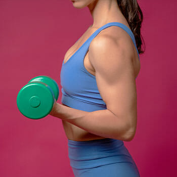 woman using a dumbbell on her arms