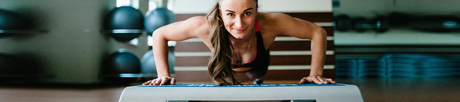 woman smiling while doing push ups