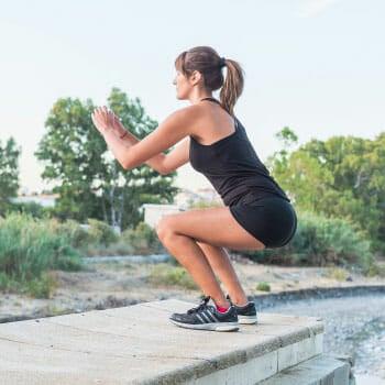 woman doing squat jumps outdoors