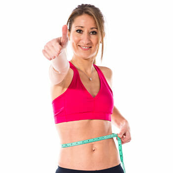 happy woman giving a thumbs and measuring her waist