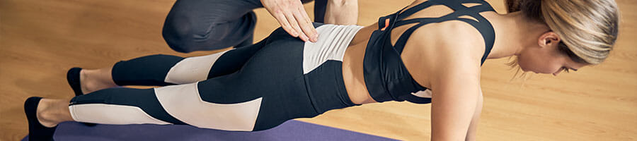 woman doing planks with a trainer