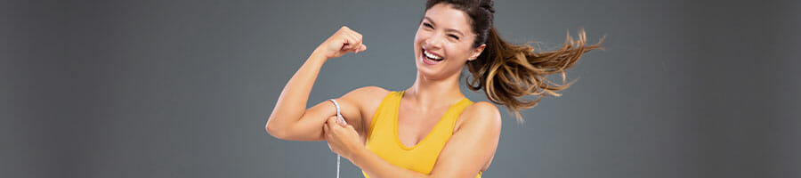 happy woman flexing her arms and measuring it