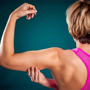 woman facing back pinching her flexed arm fat