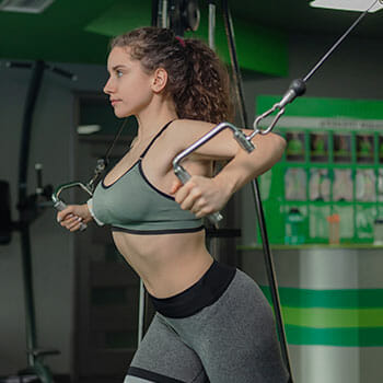 woman in a gym working out with a cable machine
