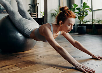 Doing a back hyperextension on an exercise ball