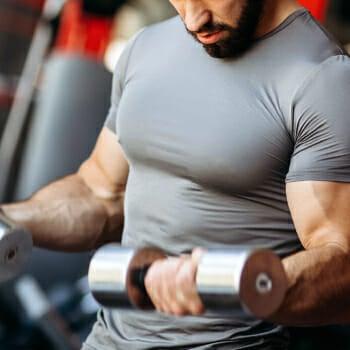 A muscular man lifting a heavy dumb bell