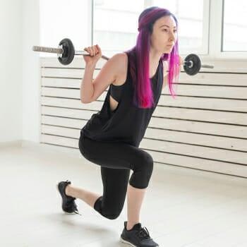 A woman doing a barbell split squats