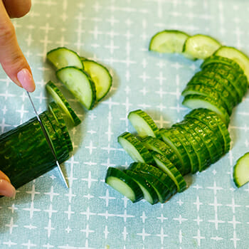 A person slicing a fresh vegetable