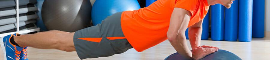 A man in orange shirt doing a push-up on a bosu