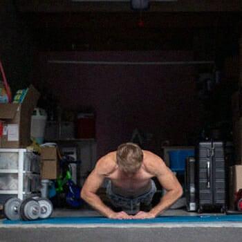 A man doing a diamond push-ups in his garage